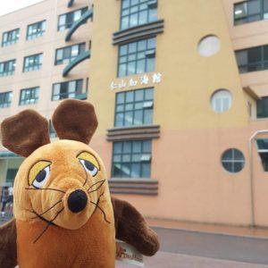 Die Maus steht vor dem Schulgebäude.