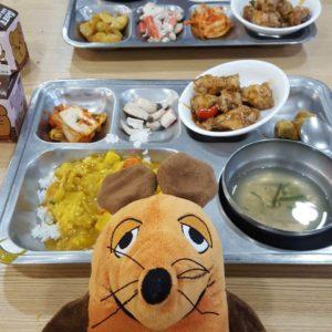 Die Maus isst Curryreis in der Schulmensa.