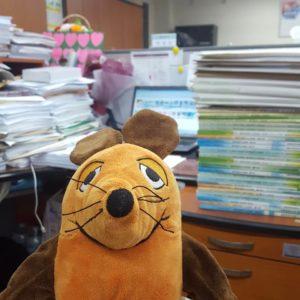 Die Maus steht am Lehrertisch.