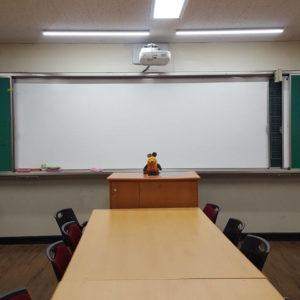 Die Maus steht am Lehrerpult.