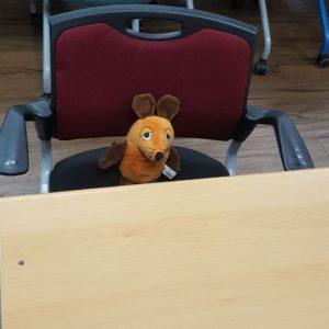 Die Maus sitzt am Schreibtisch.
