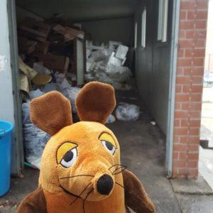 Die Maus entsorgt den Müll.