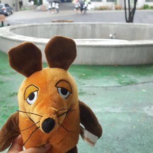 Die Maus steht vor dem Springbrunnen.