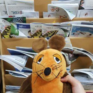 Die Maus liest Informationen über die Universitätseintrittsprüfungen.
