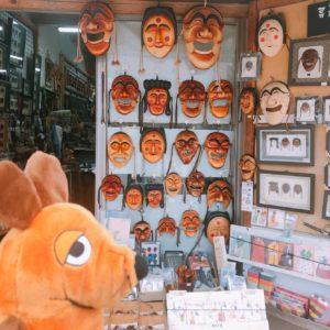 die Maus vor einem Maskengeschäft