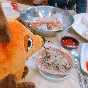 Die Maus isst gebratenen Reis aus einem Krabbenschild.